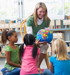 Kindergarten teacher and children looking at globe in library